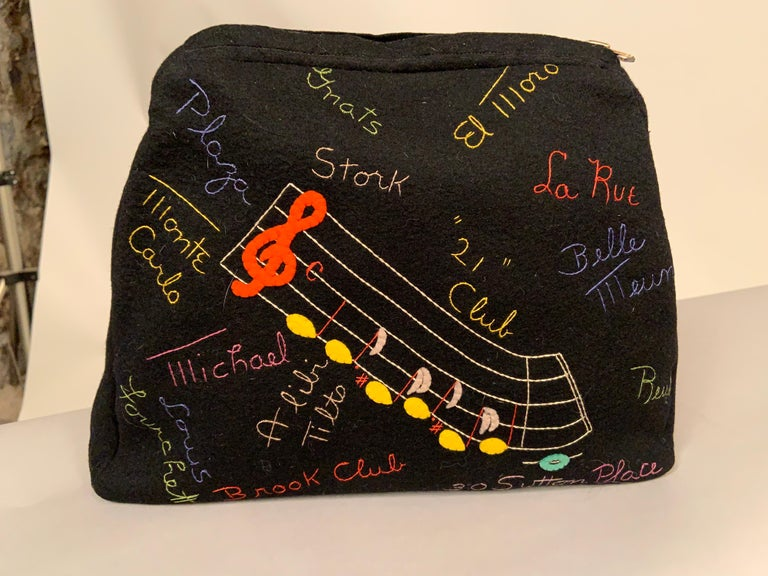 A black wool felt clutch is appliqued on the front side with a cheerful yellow checker taxi cab carrying two passengers. It is surrounded by embroidered names of chic retail stores in  New York City, vacation destinations, race tracks etc. from the