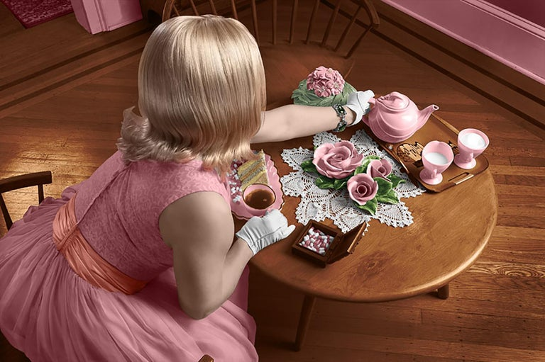 Contemporary figurative photograph  digital C-print, edition of 10 30 x 20 inches unframed  This contemporary c-print pictures a classic 1950's housewife in a beautiful pink dress and pristine white gloves enjoying a cup of tea at a beautifully set