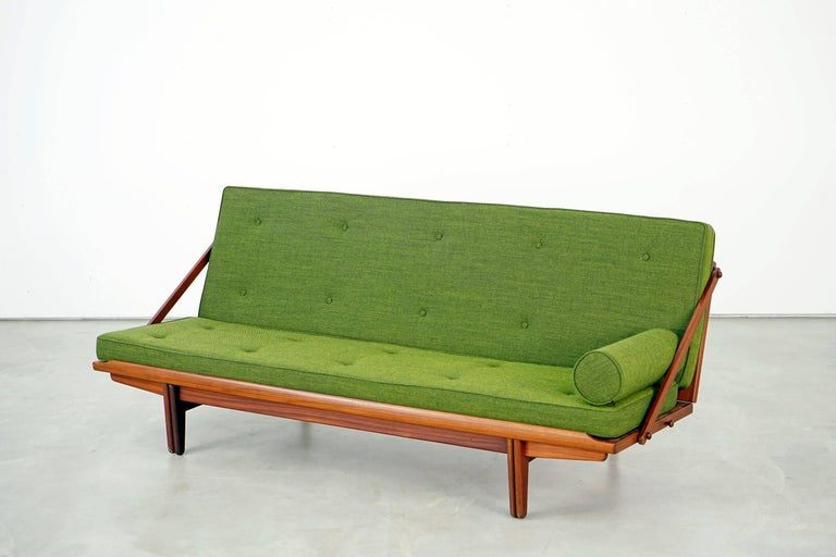 Designed by Poul M. Volther for Frem Røjle in the 1950s, the Daybed combines elegance and functionality as it unfolds easily. The teak frame is in very good condition, the cushions have been upholstered and covered with high-quality kvadrat 2 933