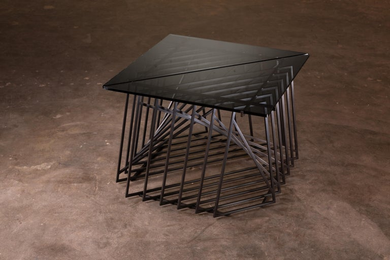 The Nexus Side Tables are a sculptural study, crafted by hand, from satin black oxide steel and gray glass. Versatile and modular, the triangular tables can be fully customized to be used independently, as a square duo, or as an asymmetric trio.
