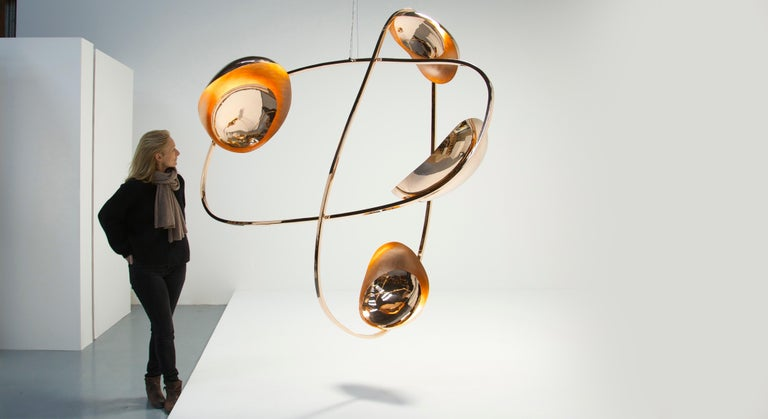 Barry's Counterpoise is composed of two polished bronze ellipses, barnacled with a series of light-emitting coques. Each coque, in turn, possesses a warm golden interior and an inset mirror polished plate. This well-ordered form is not merely