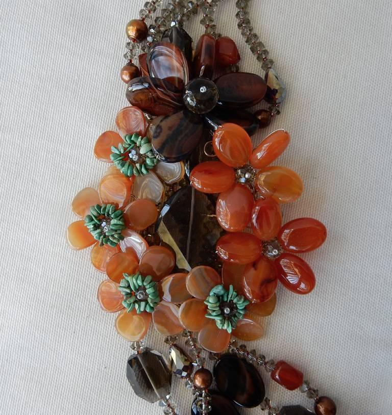 A stunning statement piece handcrafted in rich colors of orange agate flowers accented with turquoise and smoky quartz centers.  Each beaded strand graduates longer than the next, and features stations of multishaped smoky quartz, orange agate, red