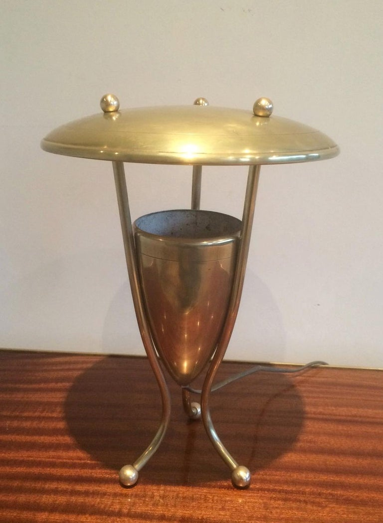 This interesting table lamp or desk lamp is made of brass. It has an interesting round reflector on top. This is a French work, circa 1950.