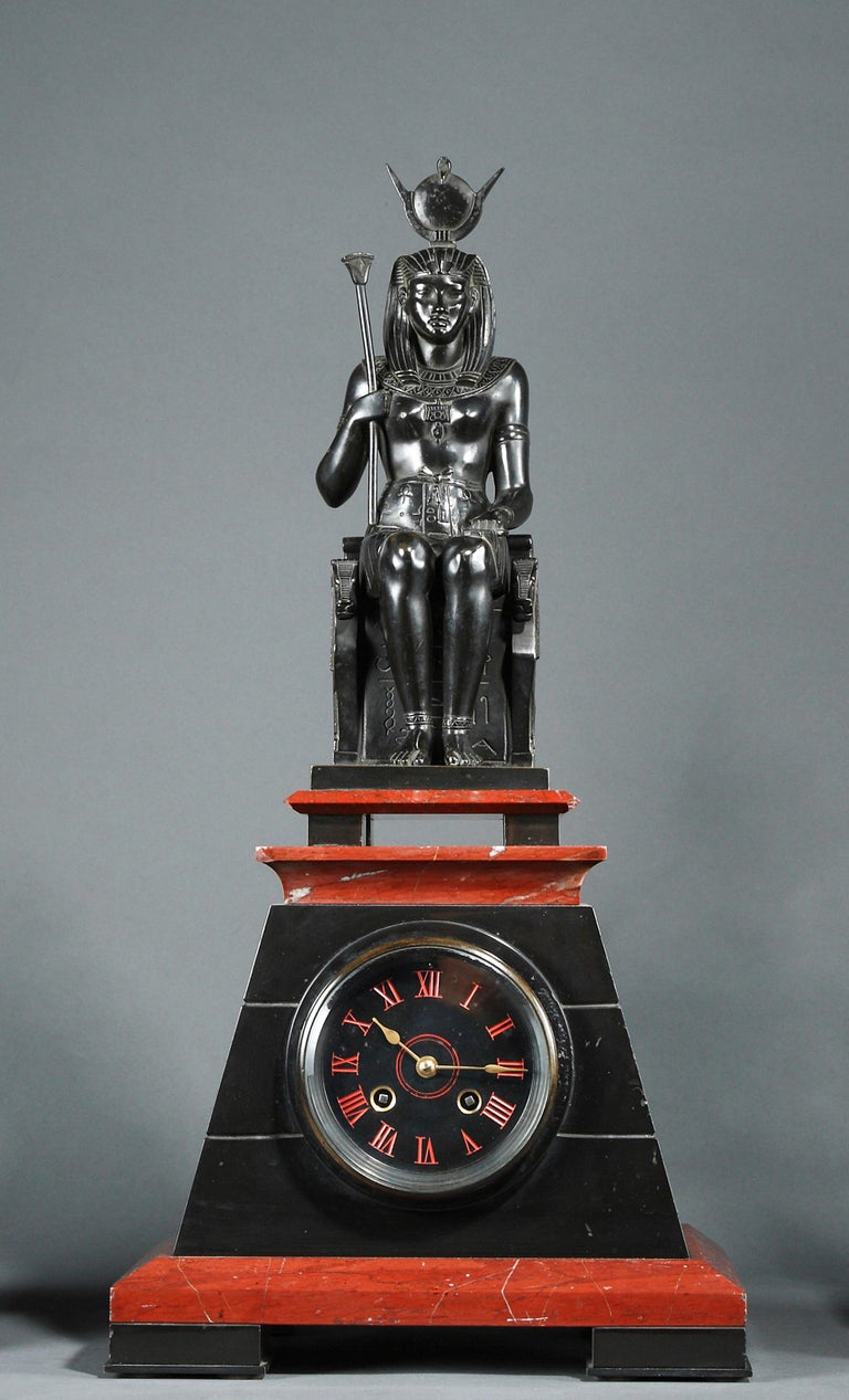 Black and red marble pyramid shaped Egyptian style clock, surmounted by a patinated bronze figure representing the Egyptian goddess Isis sitting on her throne. Wearing the Hathor hairdress (the solar disc surrounded by the sacred cow horns), she