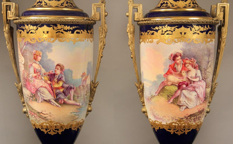 A nice pair of late 19th century gilt bronze mounted cobalt blue Sèvres style porcelain vases  The vases are decorated with finely tooled gilt reserves on a deep blue ground; the wraparound painted scenes with courting couples inspired by the fete