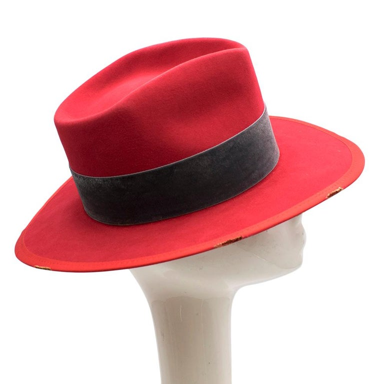 Nick Fouquet red wool hat featuring a stiff brim, a concave top, straight band, green bow detail and a signature matchstick  Please note, these items are pre-owned and may show signs of being stored even when unworn and unused. This is reflected