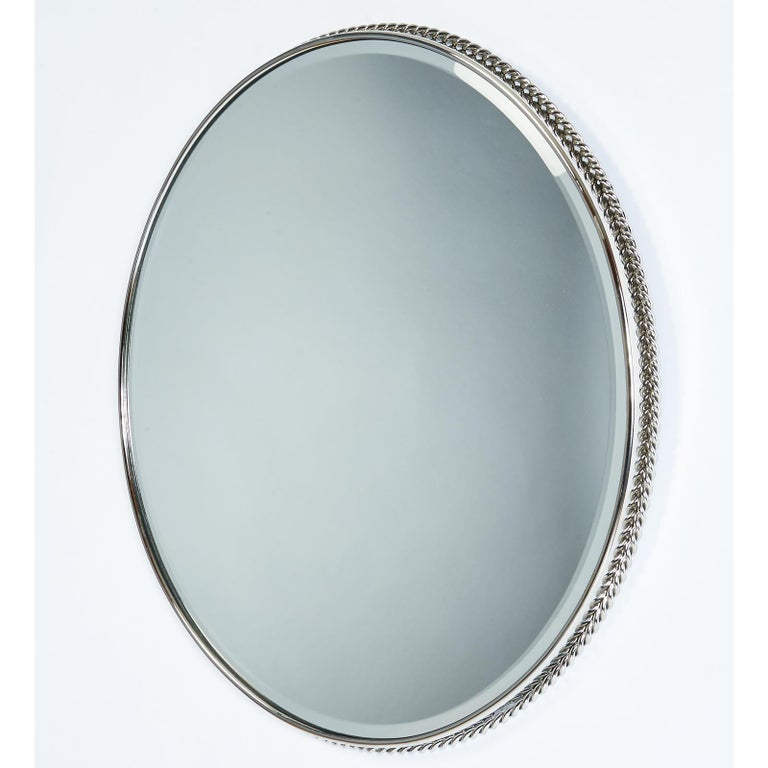 France, 1950s. Elegant nickeled bronze mirror with twisted cord decor Dimensions: 24 W x 23.5 H slightly oval.