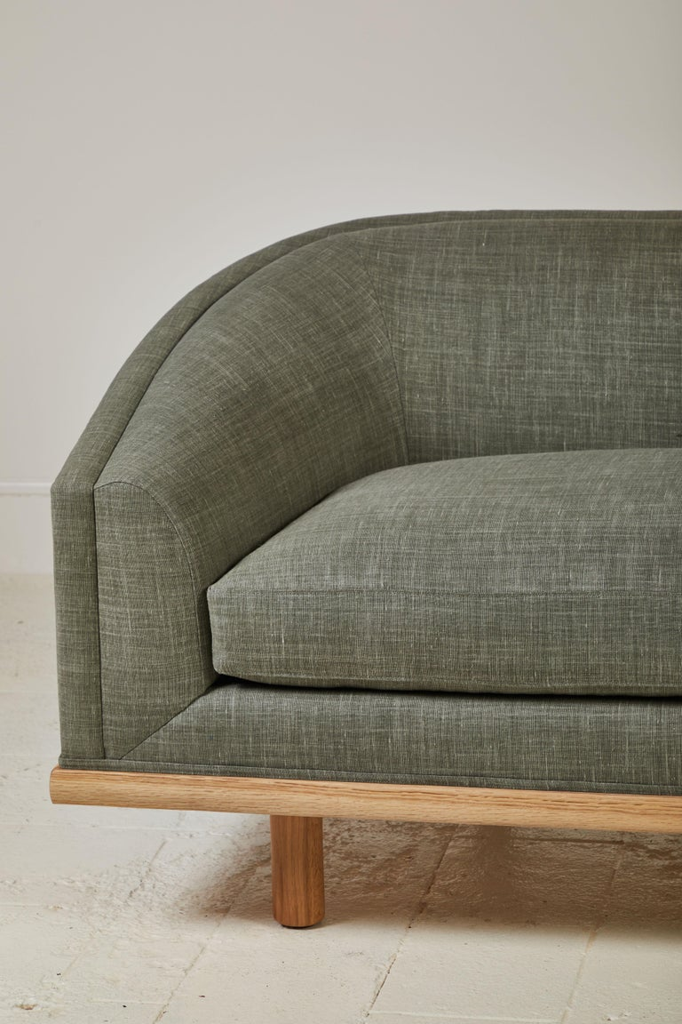 Elegant tight back sofa with curved silhouette and delicious depth. Long single seat down/feather cushion wrapping foam core, set on solid walnut framed-base atop Classic minimal cylinder legs. This specific sofa is upholstered in a dune green linen.