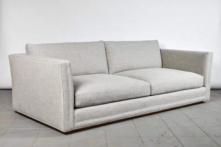 The double welt and slight fare to the modern lounge sofa make it a distinct, Classic piece. Its generous depth adds to the comfort of the down-encase foam inserts. Solid frame, hand-tied springs, and recessed solid walnut plinth shadow base present
