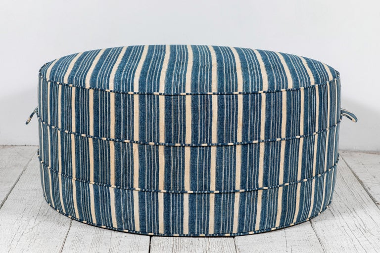 Solid wood frame and upholstered hassock with two ring piping and double handle details offers versatility in accent seating. This custom Nickey Kehoe Collection round ottoman is upholstered in vintage African striped Indigo from Burkina Faso.