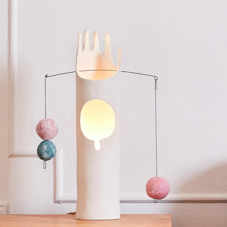 Nico Lamp is a contemporary sculptural hand-shaped stoneware ceramic table lamp in a white matte glaze and accent ceramic balls hung from a steel wire. Each lamp is individually hand-built by the artist with clay slabs, glazed, and then fired in an