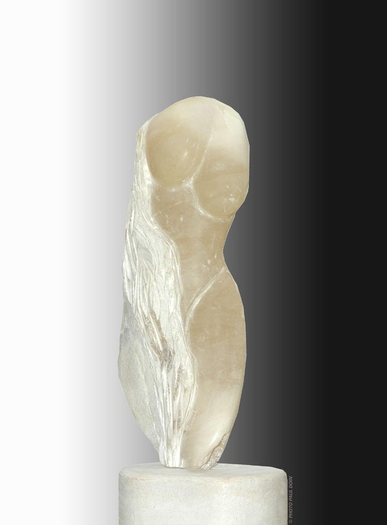 In pure white alabaster from Italy, this is a very unique piece handcarved and signed by Nicole Durand Influenced by master sculptors, Michelangelo and Rodin, Durand began her artistic journey in France, where she was born. She also lives on the