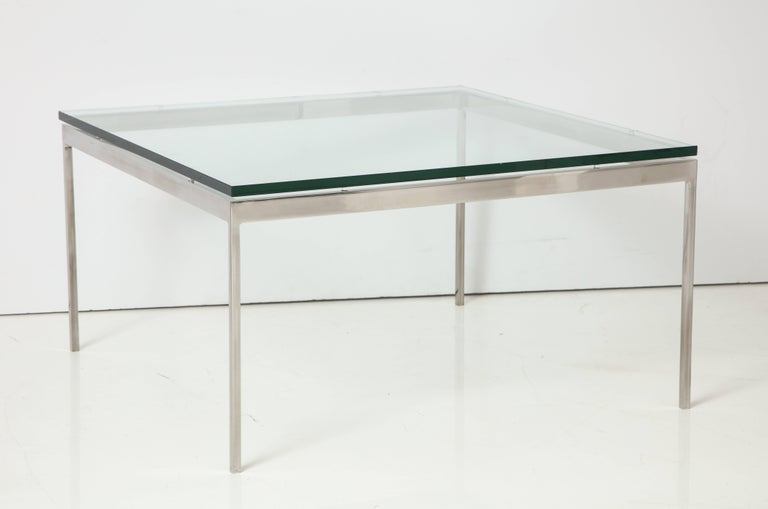 Elegantly minimalist cocktail table rendered to precise specifications in stainless steel with a 3/4 inch glass top. A Nicos Zographos design and production from his 35 series of low tables, circa 1970s. Zographos's 1960s updates on International