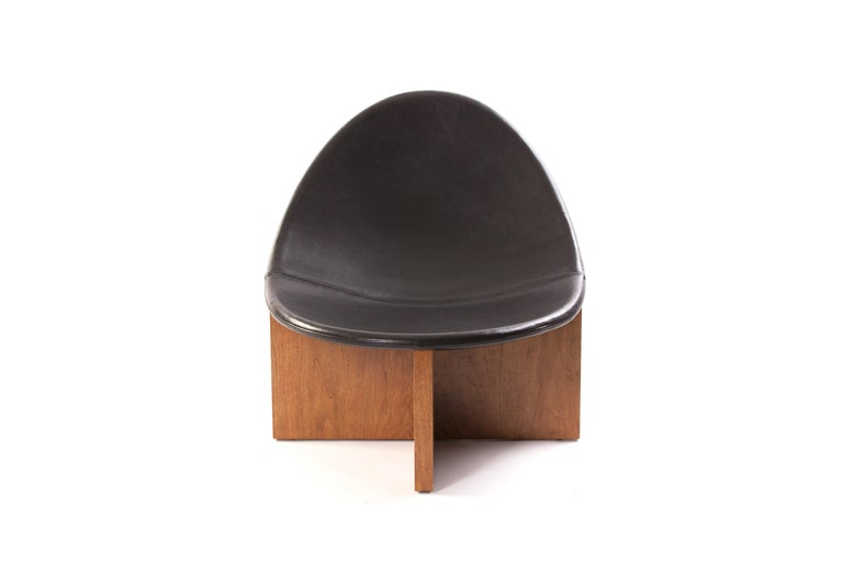 Nido lounge chair with solid walnut base and black leather upholstered seat.The Nido chair was the result of playing with the juxtaposition of shapes. The egg-like shape of the leather upholstered wood seat nesting in the cross shaped solid wood
