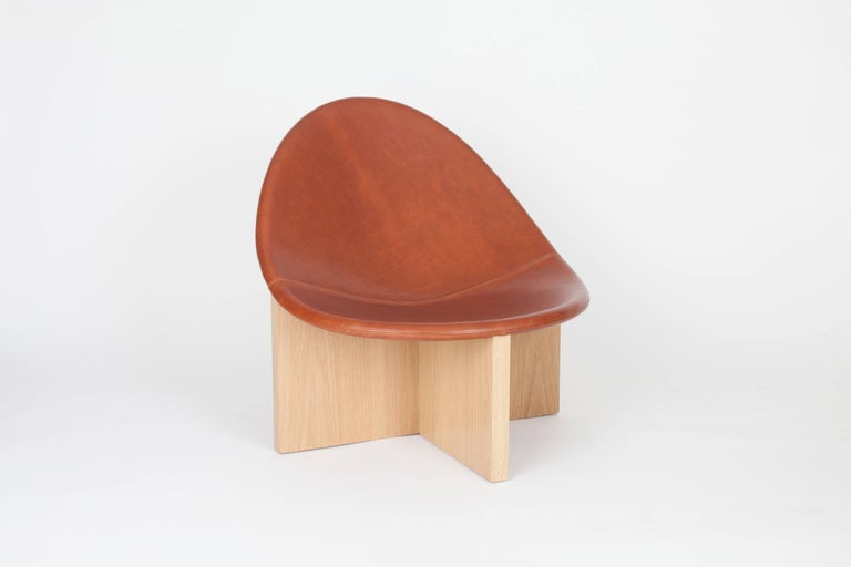 The NIDO Chair was the result of playing with the juxtaposition of shapes. The egg-like shape of the leather upholstered wood seat nesting in the cross shaped solid wood frame gives it the name NIDO, meaning nest in Spanish. The strong lines of the