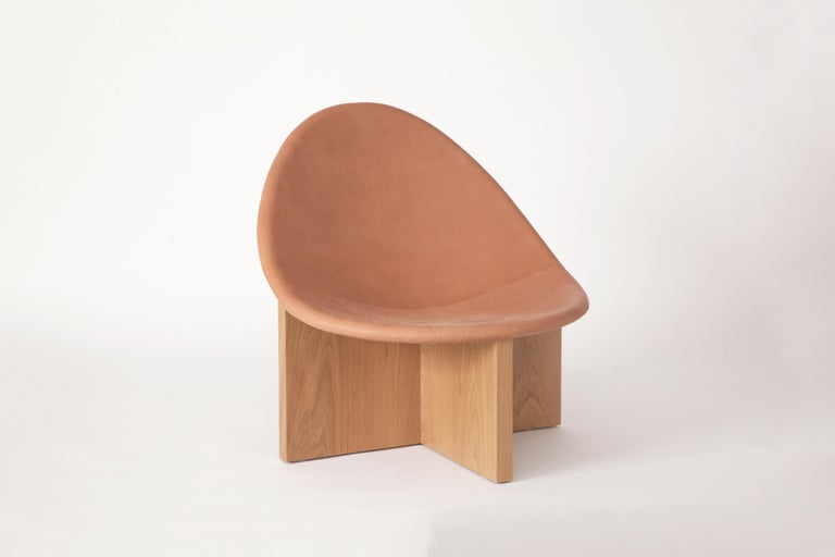 The NIDO chair was the result of playing with the juxtaposition of shapes. The egg-like shape of the leather upholstered wood seat nesting in the cross shaped solid wood frame, gives it the name NIDO, meaning nest in Spanish. The NIDO's strong lines