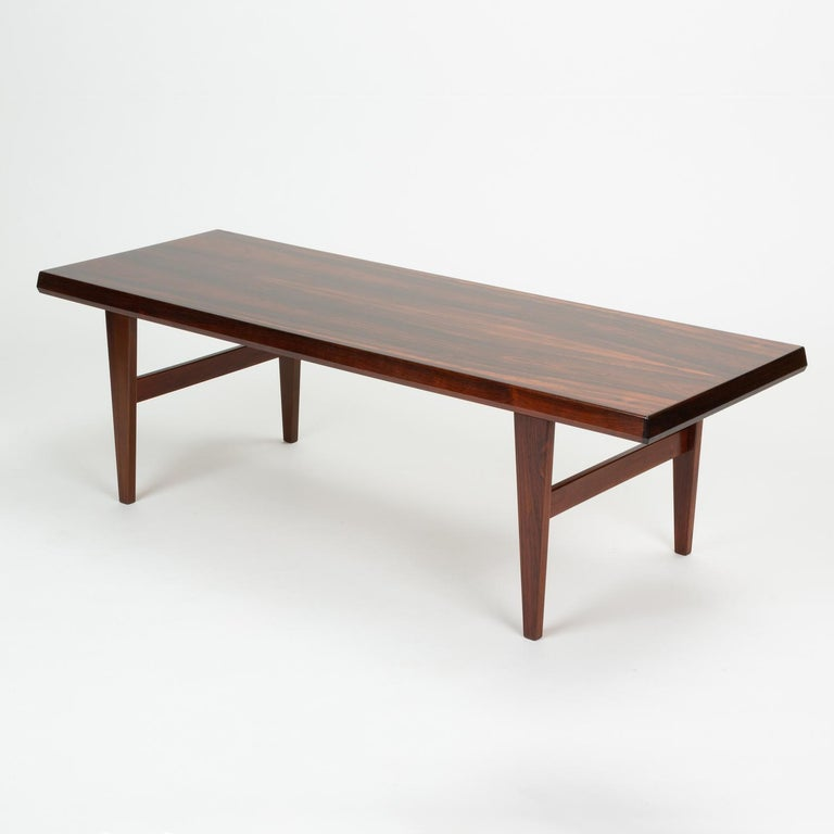 A generously proportioned, European height coffee table in highly figured Brazilian rosewood by Niels Bach, a manufacturer based in Randers, Denmark. The long tabletop has angled edges and is thick enough for the piece to double as a bench. The