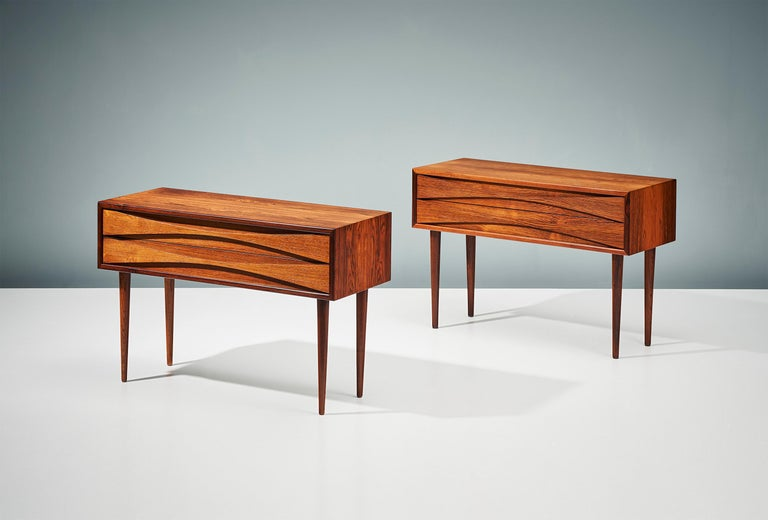 Pair of bedside cabinets, circa 1960  Rosewood cabinets by Niels Clausen for his own company NC Møbler produced in Odense, Denmark, circa 1960. Each wide cabinets has two slim drawers with elegant scalloped drawer-pulls and solid turned and