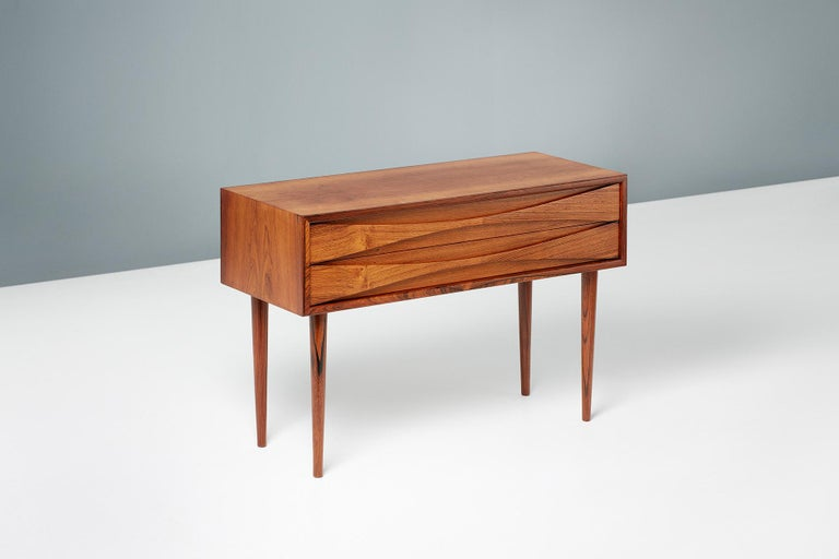Niels Clausen  Rosewood bedside cabinet, circa 1960  Rosewood cabinet by Niels Clausen for NC Mobler, Odense, Denmark. Produced, circa 1960. Two drawers with scalloped pulls and solid tapered legs.