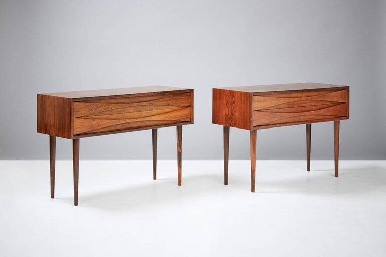 Pair of bedside cabinets, circa 1960  Rosewood cabinets by Niels Clausen for NC Møbler, Odense, Denmark. Produced, circa 1960. Two drawers with scalloped pulls and solid tapered legs.