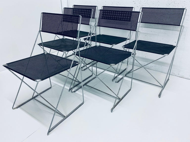 Set of 6 dining chairs in X-line, made of steel rods and black enameled perforated steel backs and seats. Designed by Niels Jorgen Haugesen for Magis. These chairs are in original condition with wear and are stackable. Made in Denmark.