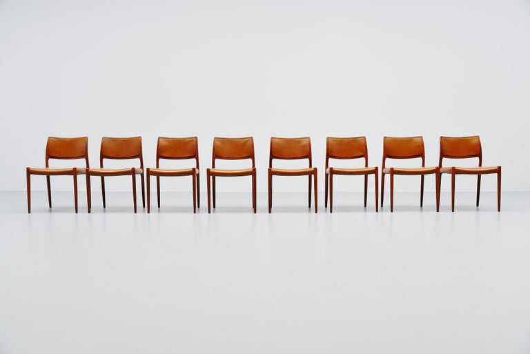 Very nice set of 8 teak dining chairs model 80, designed by Niels Moller and manufactured by J.L. Møller Mobelfabrik, Denmark 1966. The chairs have solid teak frames and original cognac leather upholstery with a very nice patina from age and usage.