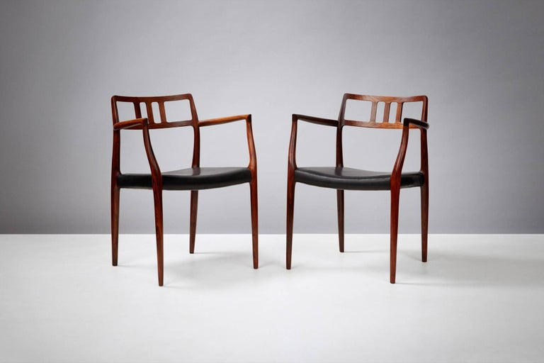 Pair of Model 64 rosewood armchairs produced by J.L. Mollers Mobelfabrik, Denmark, circa 1966. Newly covered in aniline black leather.