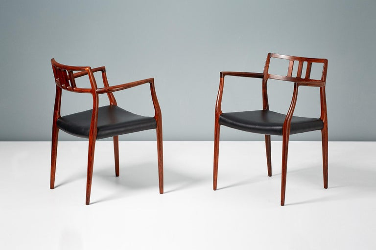 A pair of Model 64 rosewood armchairs produced by J.L. Moller Mobelfabrik in Denmark, circa 1966. The stunning rosewood frames have been refinished and the seats newly covered in premium aniline black leather.