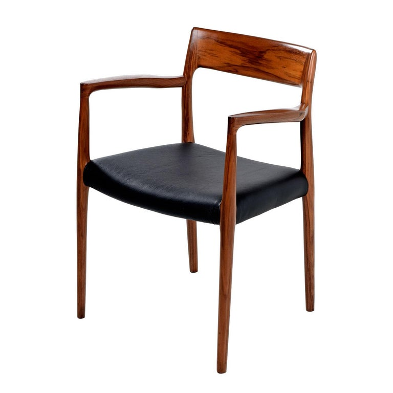 Model 57 walnut arm chair, designed by Niels O. Møller and produced by J.L Møllers Møbelfabrik. Made in Denmark, the chair bears the manufacturer label. The several decades old walnut has a rich red patina that bounces beautifully against the new