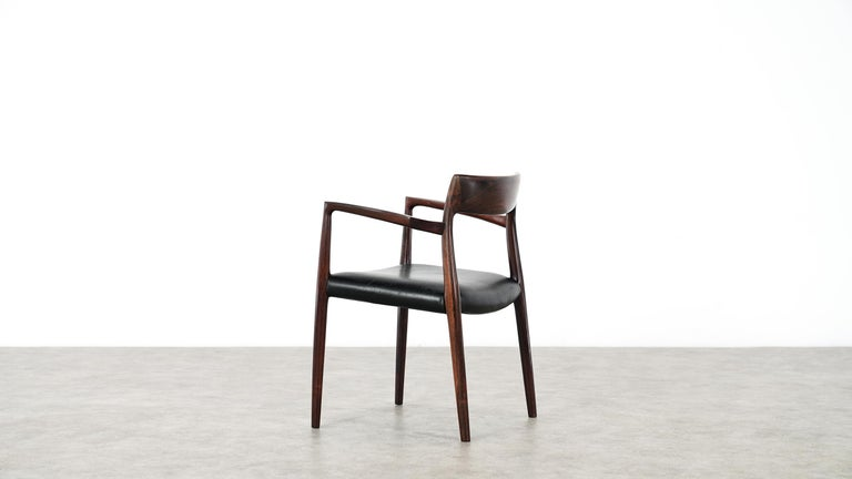 Model 57 walnut armchair, designed by Niels O. Moller and produced by J.L Mollers Mobelfabrik.  Made in Denmark, the chair bears the manufacturer label.   The several decades old walnut goes nicely with the black leather upholstery.  Elegant