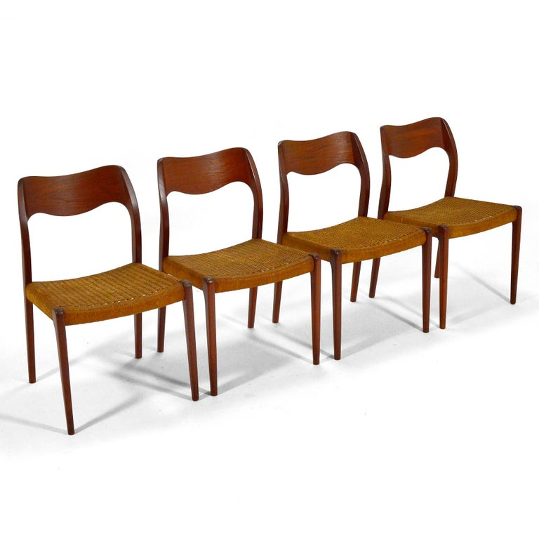 A handsome set of four model 71 dining chairs designed by Niels O. Møller and made by J.L. Møllers Møbelfabrik. The sculptural teak frames and woven paper cord seats have a beautiful patina from years of age and use.