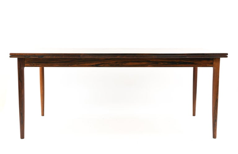 A rare, large Danish midcentury dining table designed by Niels O. Møller for J.L Møllers Møbelfabrik, circa 1960s, in rosewood with a bookmatched veneered rosewood top. A clean, refined rectangular form with rounded, tapered legs give this piece a