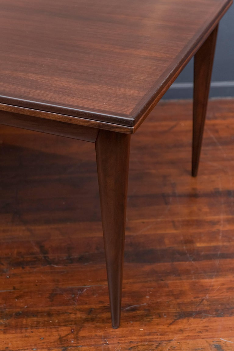 """Beautiful model #12 dining table with tapered legs and self-storing leaves by Niels Otto Møller for J.L. Møller. Signed with manufacturer's sticker and Danish control sticker. Table measures 59"""" L closed; 104"""" L fully extended."""