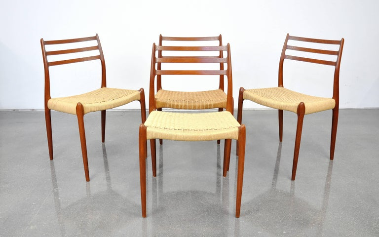 Set of four Mid-Century Danish Modern dining chairs designed in 1962 by Niels Otto Moller for J.L. Møllers Møbelfabrik in Denmark. In original condition with rich color and patina, they feature a gorgeously sculpted solid teak frame and Danish paper
