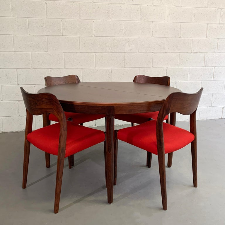 Danish modern, rosewood dining set by Niels O Moller features 4 model #71 chairs and two separate 19.5 inch leaves that extend the table to 66 inches with one leaf up to 86 inches with both leaves. The chairs measure 19.5 W x 18 D x 30.25 HT, seat
