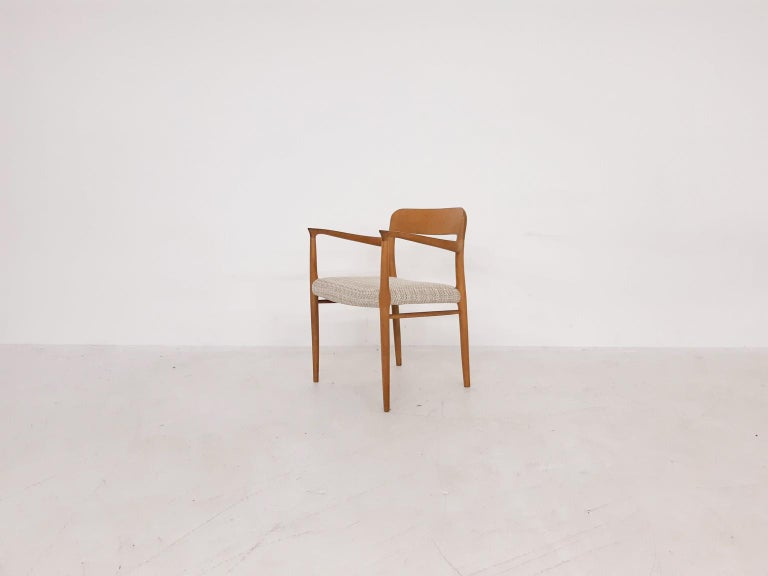 Solid oak dining chair with arm rests by Danish midcentury designer Niels Otto Møller.   This vintage example from 1959 is Model 56, one of his most popular designs nowadays. The chair is reupholstered in new off-white fabric. In good