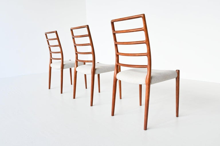 Beautiful set of three dining chairs model 82 designed by Niels Otto Moller and manufactured by J.L. Møller Mobelfabrik, Denmark, 1960. These chairs are made of solid teak wood and are upholstered with cream white Divina Melange fabric of Kvadrat.