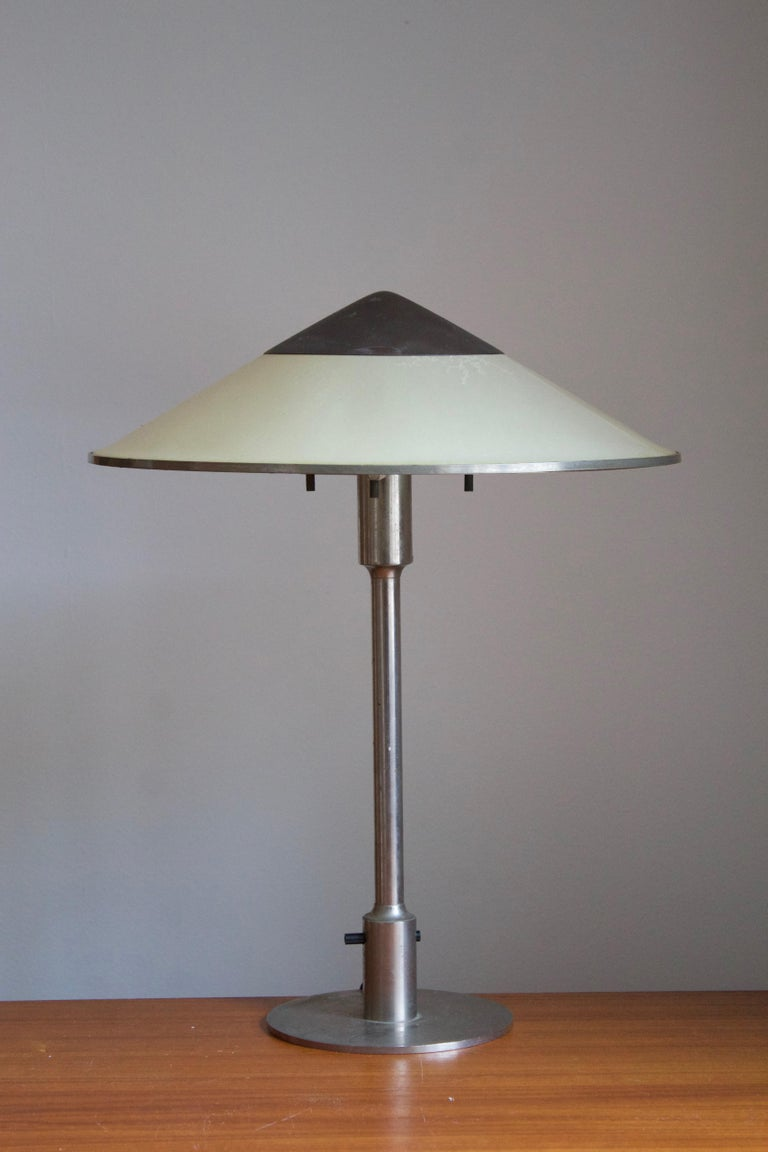 A rare and early table lamp / desk light. Designed by Niels Rasmussen Thykier, Denmark, 1930s. Features a break-through switch typical to early production examples.  In nickeled brass and waxed paper screen.