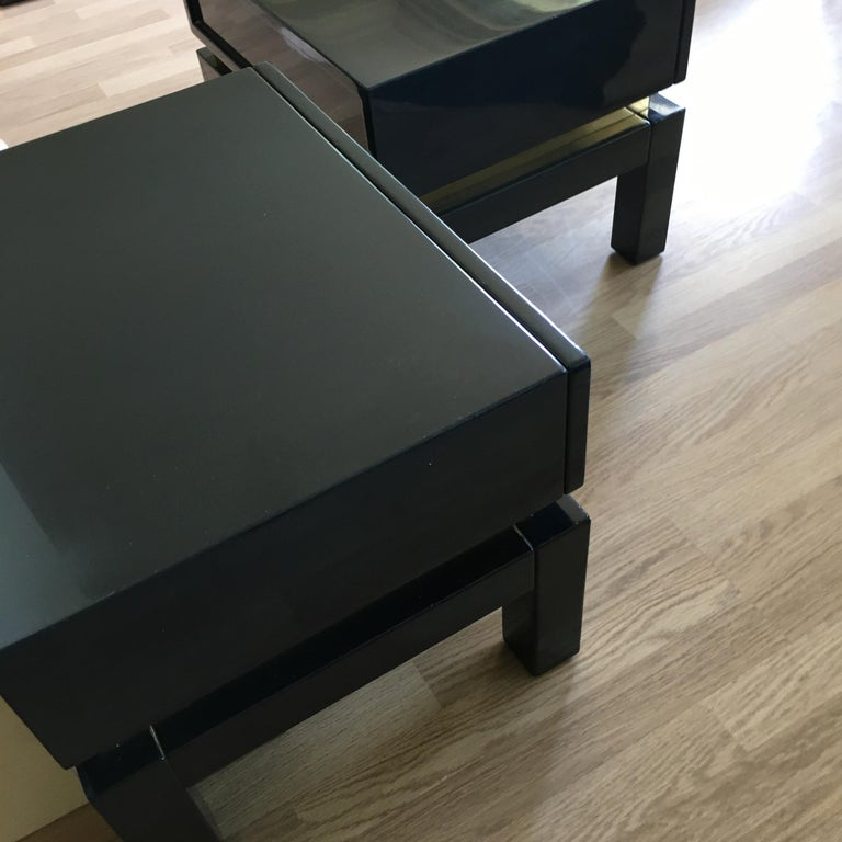 Fine dark blue lacquered side tables with brass details. A large drawer each with a geometric handle. From Maison Jansen, France 1975.