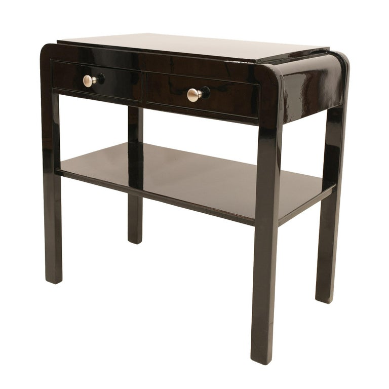 This elegant nightstand comes from Poland from early 20th century. It was renovated, finished with piano lacquer and polished to a high gloss. The table features 2 practical drawers and a shelf.