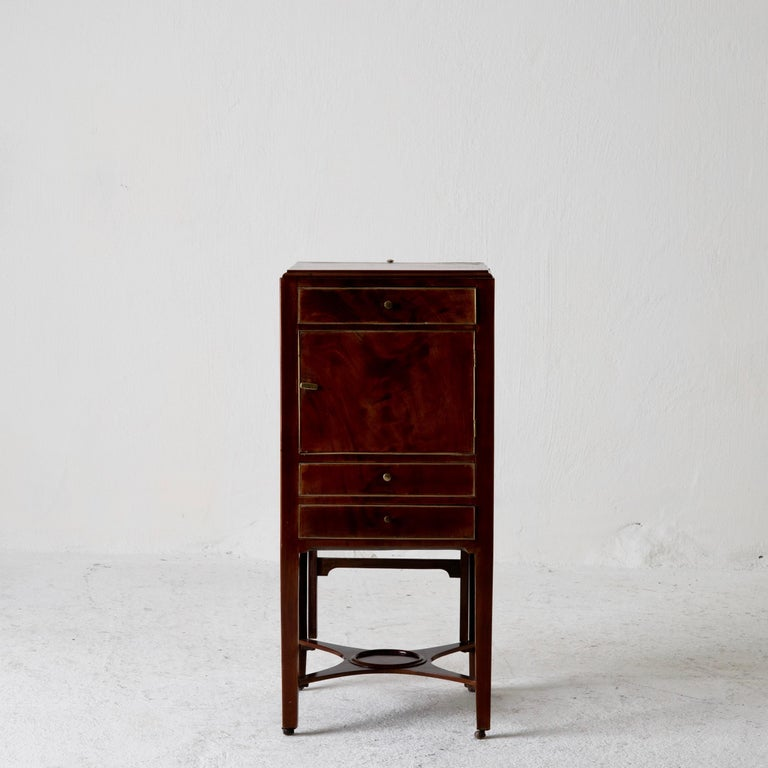 Nightstand vanity table Gustavian Swedish mahogany brass lining, Sweden. Nightstand made in Sweden during the Gustavian period 1790-1810. Made in mahogany veneer decorated with brass linings. Drawers and a cabinet. Vanity mirror hidden.