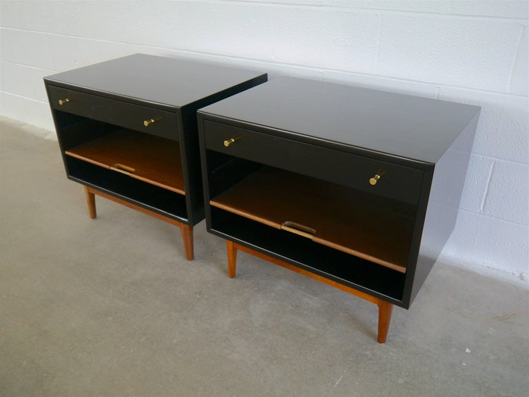 Nightstands in walnut by Kipp Stewart for Drexel. These large nightstands have drawers and an adjustable sliding shelf with raffia handles. The pulls are solid machined brass. We borrowed the finish from Dunbar pieces of the period, the cases done