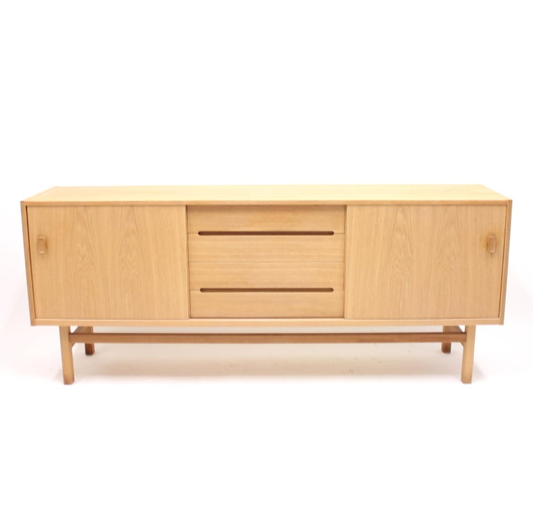 Oak sideboard, model Arild, designed by Nils Jonsson for Swedish manufacturer Troeds. Middle section with four drawers. The top drawer contains compartments for cutlery and a movable tray. All clad in a blue felt fabric. Both sides with sliding