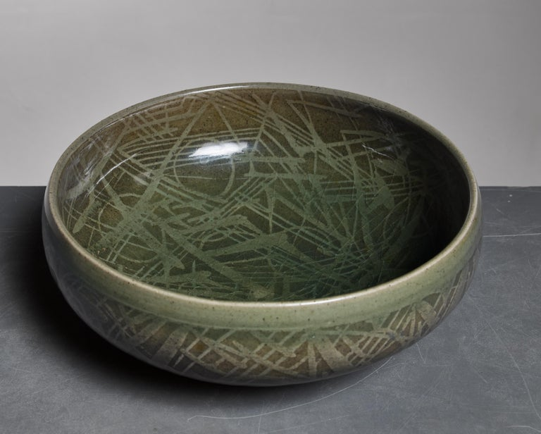 A green ceramic bowl with a wonderful striped motif in the glaze, designed by Nils Thorsson for Royal Copenhagen.  Marked by Thorsson and Royal Copenhagen and in a wonderful condition.  Nils Thorsson (1898-1975) was a Danish ceramist and