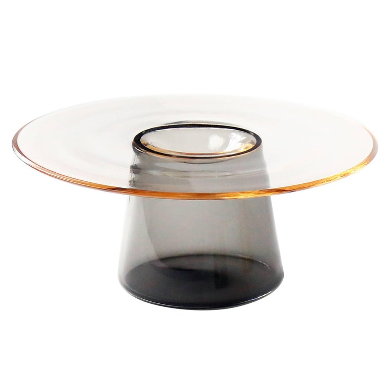 Nina Cho presents layering transparency, a new collection of handmade glass works in various scales, from an accent table to tabletop object.  The distinguishing feature of this collection is the recessed curve at the centre of each top plate's