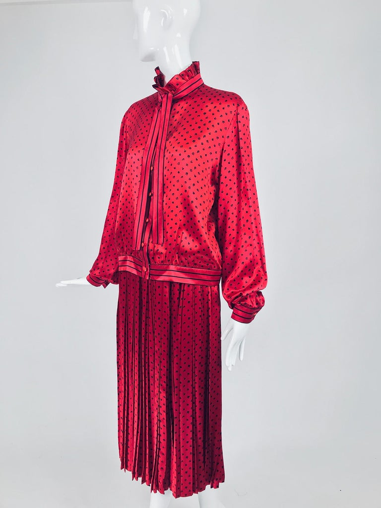 Nina Ricci red silk satin printed blouse and skirt set from the 1980s. Gorgeous candy apple red silk satin is printed with tiny abstract black print. The blouse has a pleated high neckline collar with an attached narrow stripe bow tie. Long full