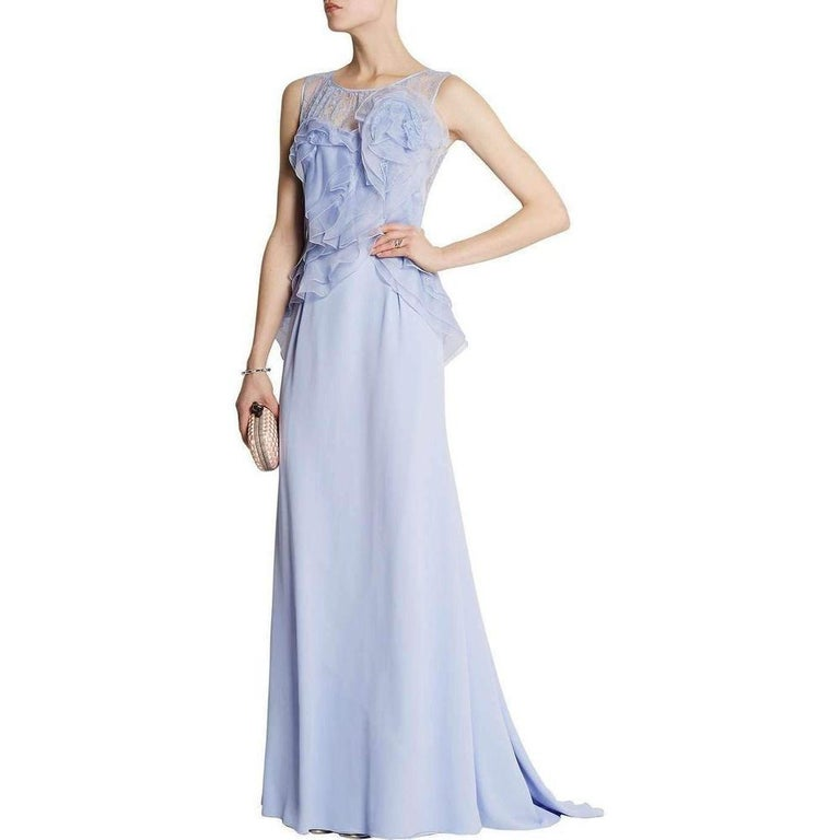 Nina Ricci's lavender silk crêpe sleeveless gown is flou tailored with layers of frothy ruffles running in a diagonal across the bodice. The floor-length gown is styled with a lavender lace back and lavender lace gathered front neckline. Jewel