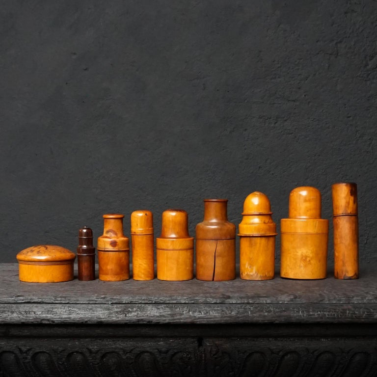Very decorative medical curiosity cabinet set of nine 19th century Victorian English and German treen turned boxwood bottle holders.  These containers were used for protecting delicate items such as glass apothecary bottles, perfume bottles,