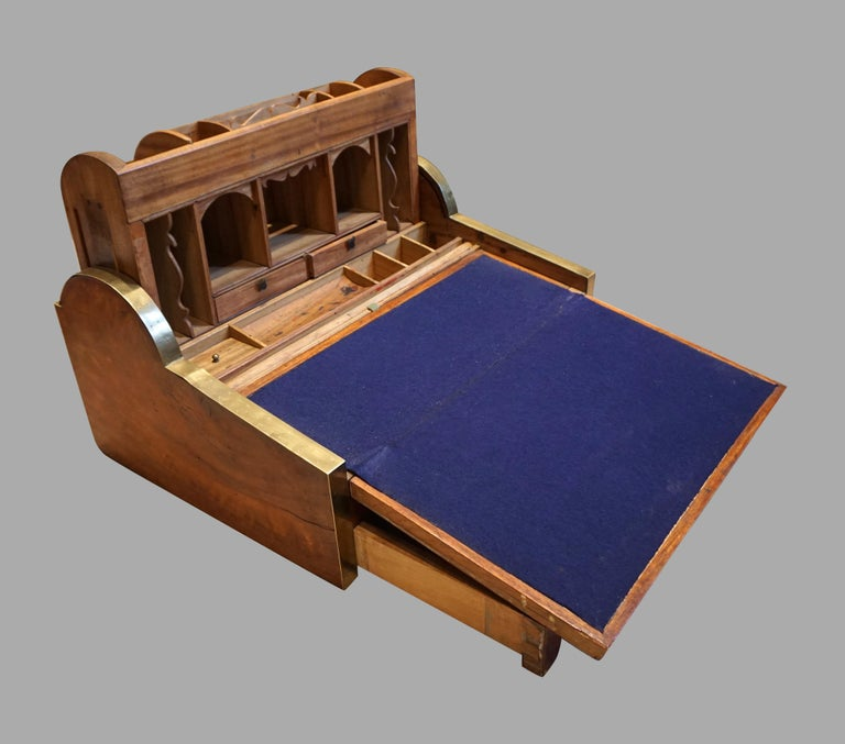 A Chinese export solid camphorwood brass inlaid and banded writing slope, the tambour activated by retracting the central drawer to reveal a rising section containing a variety of small drawers and cubby holes, the sloped writing surface lined in