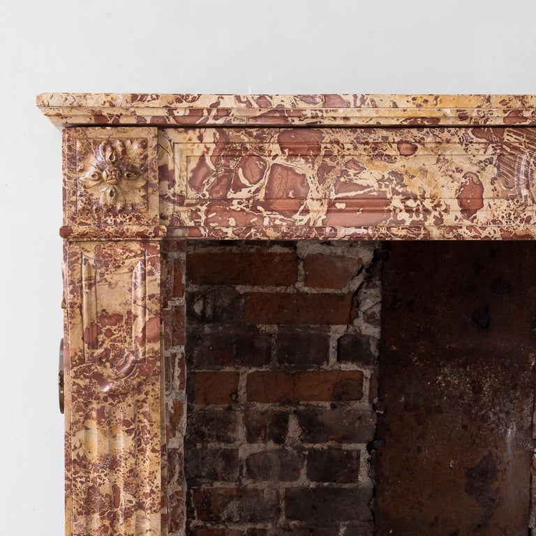 19th century French Breche fire surround, in the Louis XVI style, the paneled frieze centred by foliate boss, the paterae corner-blocks above stop-fluted console jambs, on block feet.  Measures: Aperture width 112cm x 88.5cm high.
